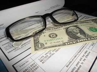 a dollar bill with glasses on top of a piece of paper